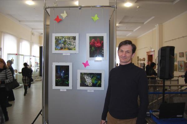 Игорь Колганов у стенда со своими весенними фотоработами на открытии выставки
